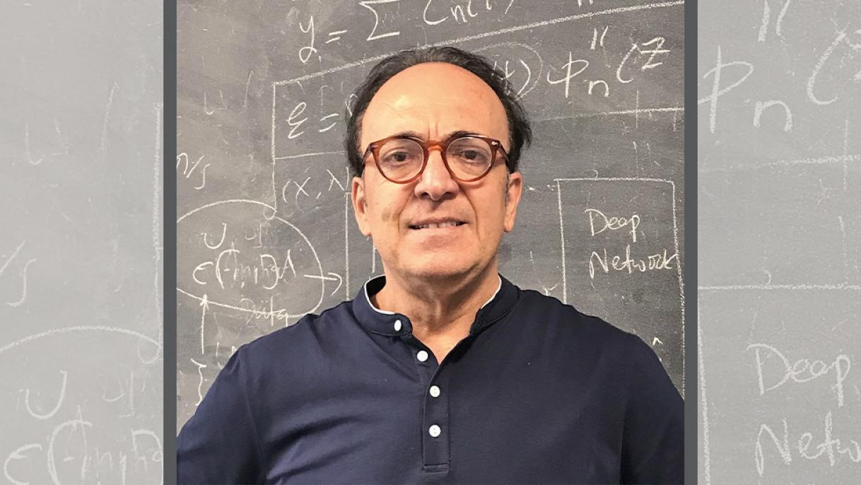 George Karniadakis in front of blackboard