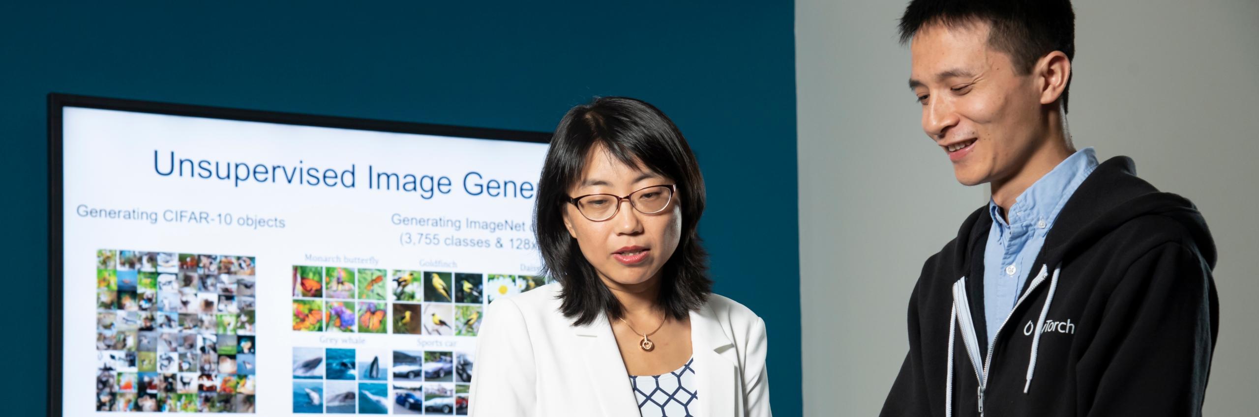 A grad student looks at a computer with Professor Hai Li
