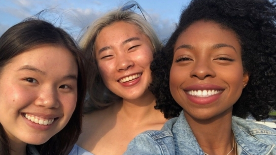 group of three smiling students
