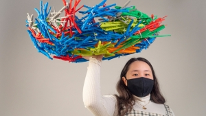 student holding colorful 3-D printed hawk's nest