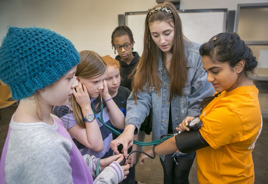 Students learn how to use a blood pressure cuff